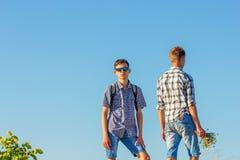 Deux jeunes types contre le ciel, des relations les uns avec les autres photos libres de droits