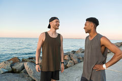Deux jeunes types de sourire dans les vêtements de sport parlant tout en se tenant Images stock