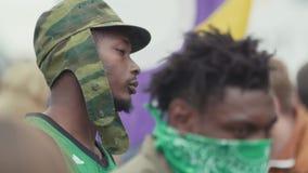 Deux jeunes types noirs songeurs de bandit s'asseyant à l'événement extérieur serré banque de vidéos