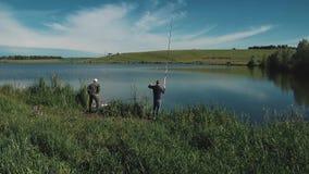 Deux jeunes types pêchent sur le lac banque de vidéos