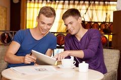 Deux jeunes types parlant en café Image libre de droits