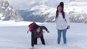 Deux jeunes voyageurs enthousiastes de femmes sautant heureusement dans la neige en dolomites clips vidéos