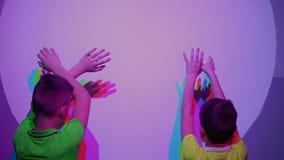 Deux jeux de garçons avec les ombres colorées