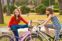 Deux jolies adolescentes ayant l'amusement sur des bicyclettes Photographie stock libre de droits