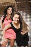 Deux jolies amies à la fin de sourire de danse de partie  Photo libre de droits
