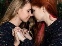 Deux jolies amies de lesbiennes embrassant et étreignant dans une atmosphère confortable Image libre de droits