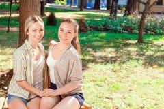 Deux jolies amies s'asseyant en parc Image stock