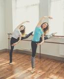 Deux jolies femmes convenables font l'exercice de ballet Photographie stock