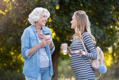 Deux jolies femmes de sourire buvant du café en parc Photographie stock libre de droits