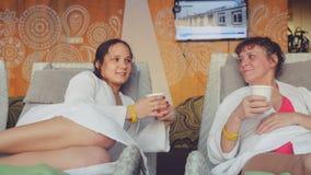 Deux jolies femmes fille et maman détendent dans un centre de station thermale, parler et une tasse de boissons de thé Photo stock