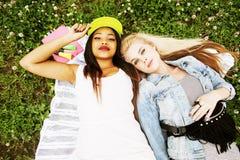 Deux jolies filles d'école sur le sourire heureux d'herbe, hav de meilleurs amis Photographie stock libre de droits