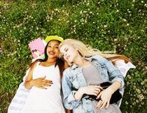 Deux jolies filles d'école sur le sourire heureux d'herbe, hav de meilleurs amis Image libre de droits