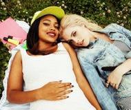 Deux jolies filles d'école sur le sourire heureux d'herbe, hav de meilleurs amis Image stock