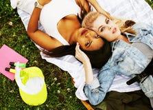 Deux jolies filles d'école sur le sourire heureux d'herbe, hav de meilleurs amis Photographie stock