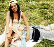 Deux jolies filles d'école sur le sourire heureux d'herbe, meilleurs amis ayant l'amusement, concept de personnes de mode de vie Photo stock