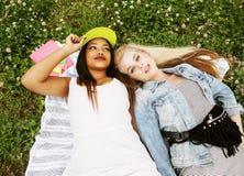 Deux jolies filles d'école sur le sourire heureux d'herbe, meilleurs amis ayant l'amusement ensemble, concept de personnes de mod Images stock