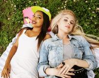 Deux jolies filles d'école sur le sourire heureux d'herbe, meilleurs amis ayant l'amusement ensemble, concept de personnes de mod Photographie stock