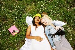 Deux jolies filles d'école sur le sourire heureux d'herbe, meilleurs amis ayant l'amusement ensemble, concept de personnes de mod Image libre de droits