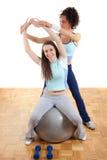 Deux jolies filles de forme physique avec la bille et les poids photographie stock libre de droits