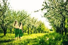Deux jolies filles heureuses marchant sur les pommiers font du jardinage Photo stock