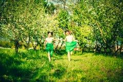 Deux jolies filles heureuses marchant sur les pommiers font du jardinage Image libre de droits