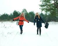 Deux jolies filles heureuses marchant un jour de l'hiver Photographie stock