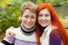 Deux jolies filles marchant en parc d'automne Photographie stock