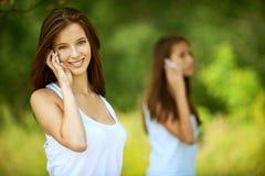 Deux jolies filles parlant sur la cellule Photographie stock