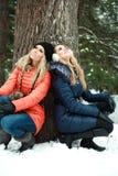 Deux jolies filles rêvantes s'asseyant sous l'arbre Photos stock