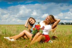 Deux jolies filles s'asseyant sur le champ d'herbe avec le rouge Photographie stock