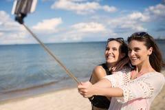 Deux jolies filles se prenant la photo sur la plage Photo stock