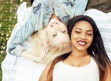 Deux jolies filles sur le sourire heureux d'herbe, meilleurs amis ayant l'amusement ensemble, concept de personnes de mode de vie Image stock
