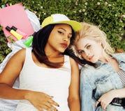 Deux jolies filles sur le sourire heureux d'herbe, meilleurs amis ayant l'amusement ensemble, concept de personnes de mode de vie Photos stock