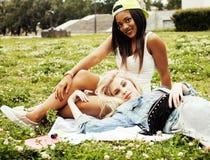 Deux jolies filles sur le sourire heureux d'herbe, meilleurs amis ayant l'amusement ensemble, concept de personnes de mode de vie Photo stock