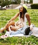 Deux jolies filles sur le sourire heureux d'herbe, meilleurs amis ayant l'amusement ensemble, concept de personnes de mode de vie Photographie stock