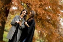 Deux jolies jeunes femmes à l'aide du téléphone portable dans la forêt d'automne photo stock