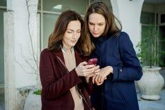 Deux jolies jeunes femmes dans un bleu et un claret regardant le téléphone dedans Images stock