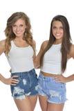 Deux jolies jeunes femmes posent en réservoirs et denim blancs Images libres de droits