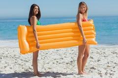 Deux jolis amis tenant le matelas d'air Images libres de droits