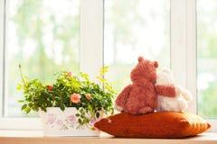 Deux jouets d'ours de nounours d'embrassement se reposant sur le fenêtre-filon-couche Images stock