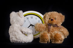 Deux jouets de petits animaux d'ours et l'horloge Photos stock
