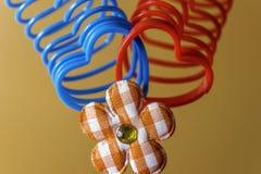 Deux jouets furtifs en forme de coeur se sont entrelacés avec le décor de fleur de plaid Photos stock