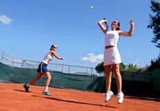 Deux joueurs de tennis féminins jouant des doubles au soleil. On est sautant et s'étirant pour la bille. photographie stock libre de droits