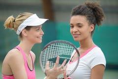 Deux joueurs de tennis féminins de sourire attirants se tenant extérieurs Photos libres de droits