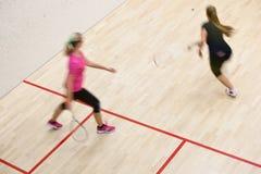 Deux joueurs féminins de courge dans l'action rapide sur une cour de courge Images libres de droits