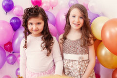Deux joyeuses amies posant sur le contexte de ballons Image stock