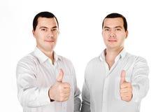 Deux jumeaux attirants de jeunes hommes avec des pouces vers le haut Photographie stock