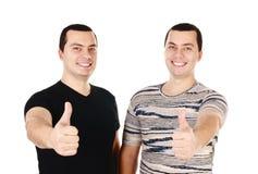 Deux jumeaux attirants de jeunes hommes avec des pouces vers le haut d'isolement Photo libre de droits