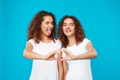 Deux jumeaux de filles montrant le coeur avec remet le fond bleu Photo libre de droits