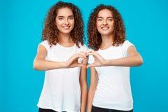 Deux jumeaux de filles montrant le coeur avec remet le fond bleu Photos libres de droits